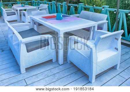Al fresco cafe with white rattan wicker armchairs and tables on summer terrace