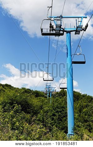 Cable car to the top of a wooded hill against blue sky