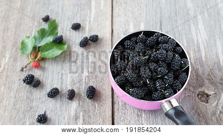 black mulberry berries in a pink pot on a wooden table. in the background are mulberry berries and sprig with ripened berries.