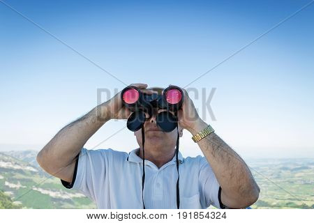 man looking through field glasses in front of blue sky and mountain range