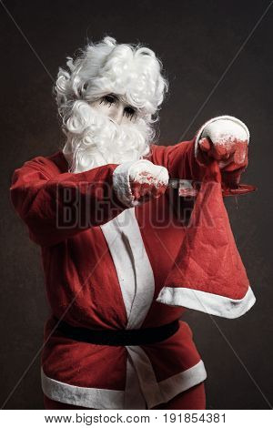 Evil Santa Claus cut with bloody knife his christmas hat