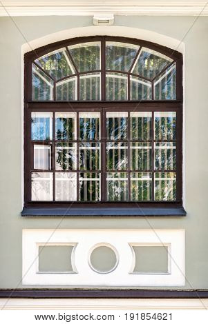 A window with a wooden lattice on the facade of the building of the naval school named after Admiral Makarov. From the series window of Saint-Petersburg.