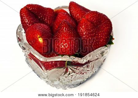 Berries of ripe juicy fresh sweet strawberries in a transparent crystal vase on a white background.