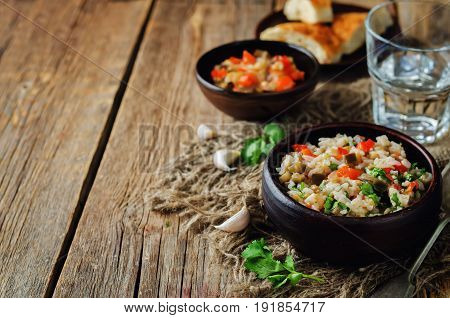 Red bell pepper eggplant cilantro rice on a wood background