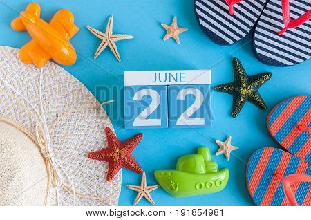 June 22nd. Image of june 22 calendar on blue background with summer beach, traveler outfit and accessories. Summer day.