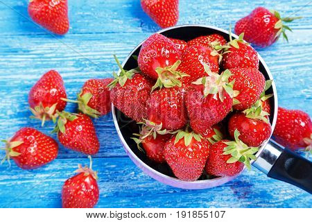 Ripe red strawberries on wooden table in natural background