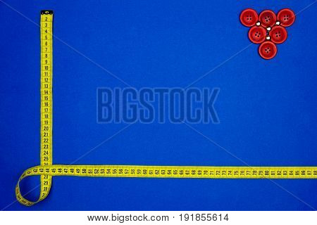 Yellow measuring tape and triangle made of red buttons isolated on blue background