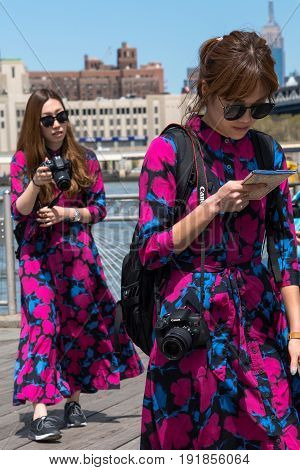 New York City United States - April 23 2017: Two asian women tourists dressing the same way walking at Dumbo waterfront.