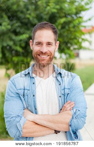 Casual guy with a denim shirt relaxed in a park