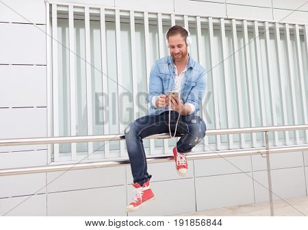 Casual guy with a denim clothes in the street listening music with his mobile