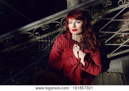 Beautiful young woman in wool red scarf sitting on old house stairs. Early fall. Outside shot. Ambient light. Closeup portrait. Copy space.