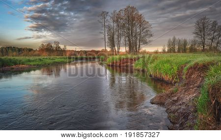 A beautiful river landscape on a wild summer day with trees and green grass on the horizon with gray clouds. Green nature and a quiet river creek in central Europe belarus