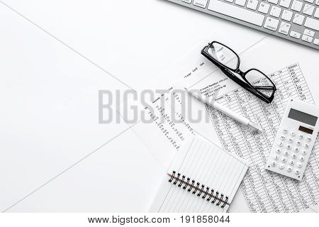 Business report preparing with calculator and glasses on white office desk background top view mock up