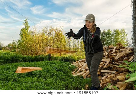 A woman throws logs during the preparation of firewood for the winter. In the background are trees and a pile of firewood.