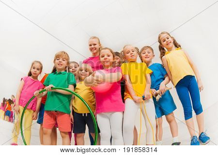 Portrait of happy kids in sportswear and female gymnastics coach, holding sports equipment, standing together in gym