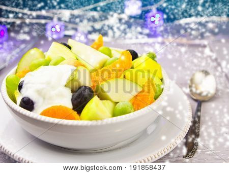 Pear, apple, orange and grapes fruit salad with yoghurt sauce