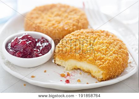 Fried breaded camembert with cranberry sauce on white plate