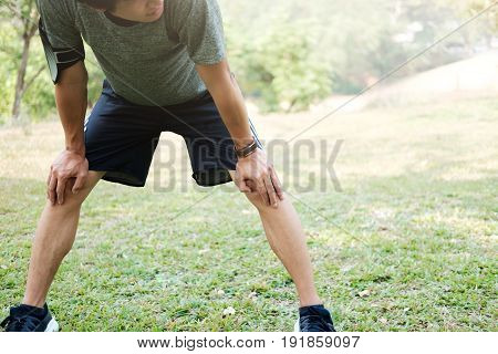 Athlete Resting On Green Glass In Park At Sunset After Running With Bottle Of Water