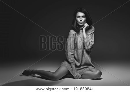 beautiful girl in oversize grey sweater sitting on floor. studio portrait on dark background. copy  space. monochrome
