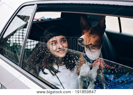 Selective focus shot of pretty young woman and her pet dog sit together inside a car and look on the rain outside