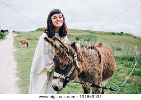 Happy and optimistic woman unites with nature by caressing funny cute donkey hugs him and laughs into camera