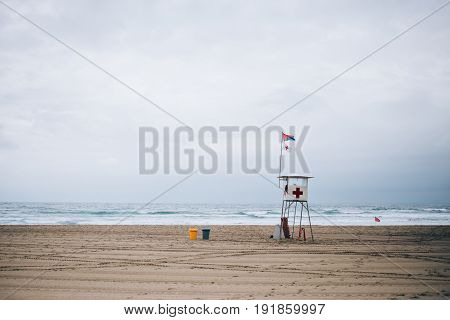 Photo of beach lifeguard tower on gloomy rainy and cloudy windy day with high hazard danger of strong current for surfers and swimmers
