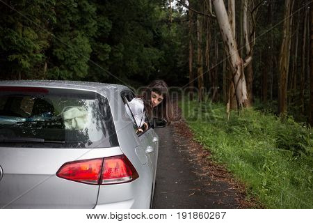 Cute petite woman looks out of car window on rainy forest road from a little hybrid vehicle