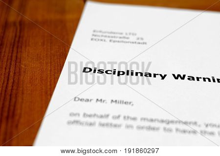 A letter on a wooden table - disciplinary warning