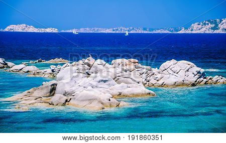 Granite rocks in sea, amazing azure water, white sailboats in background near Porto Pollo, Sardinia, Italy.