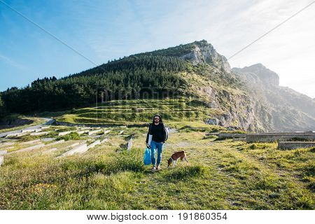 Urban nomad adventurer with backpack walks next to seaside cliffs and mountains in amazing nature scenery with best friend dog of basenji pure breed