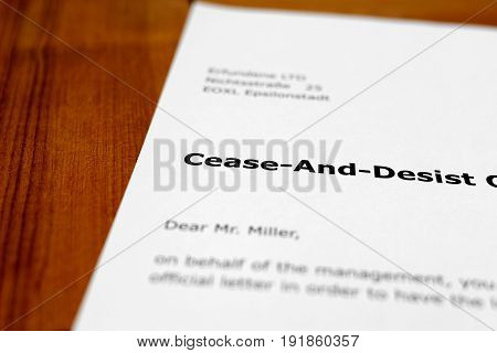A letter on a wooden table - cease and desist