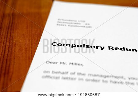 A letter on a wooden table - compulsory redundancy