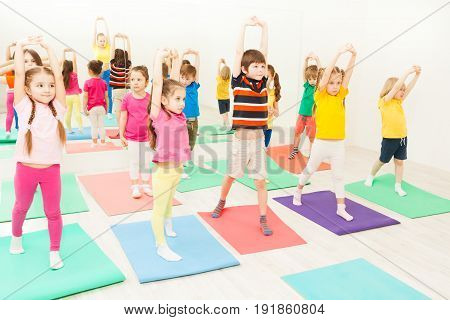Big group of 5-6 years old kids stretching and exercising during gymnastic lesson in gym