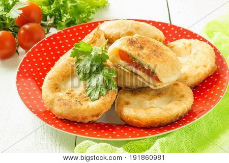 Delicious homemade pies with tomatoes cheese parsley and dill. Baking with vegetables. On white wooden table is a plate with pies on green napkin fresh cherry tomatoes and lettuce