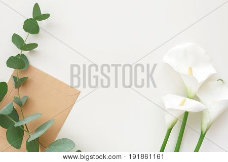 Flowers, eucalyptus and craft envelope on a white background, top view. Place for text
