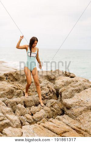 Beautiful Girl In Blue Swimsuit Walk On Big Stone.