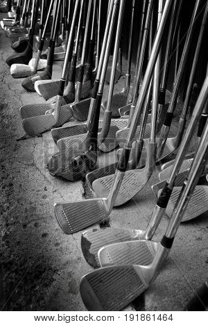 Old golf clubs leaning against wall