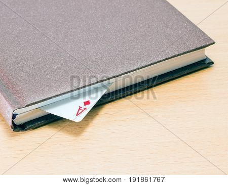 The ace of diamonds as a bookmark in a solid diary in hardcover it symbolizes success in business