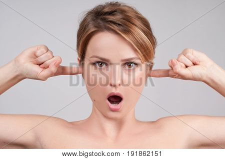 Woman With Open Mouth, Closing Her Ears With Fingers.