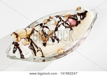 banana split on white backgroung. Dessert with a topping of chocolate cream and walnuts. in a glass dessert bowl