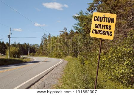Golfers crossing sign on rural highway with copy space