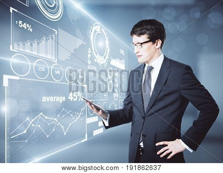 Side view of handsome young businessman using tablet in blurry interior with digital business screen. Fintech concept. 3D Rendering
