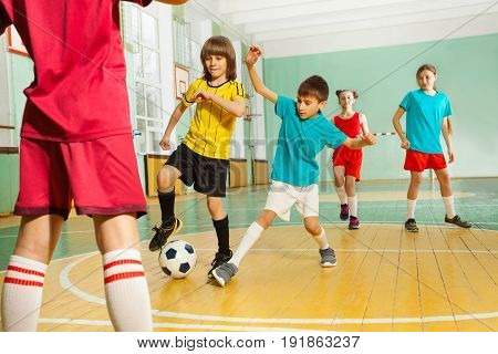 Portrait of preteen boys and girls playing football in school gymnasium