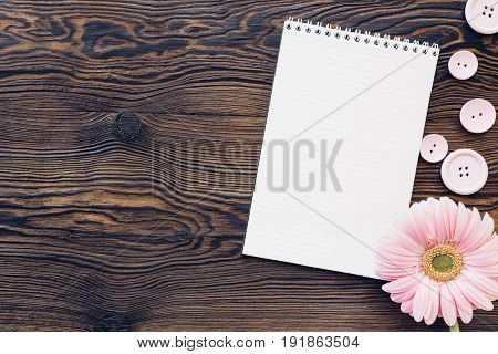 flat lay pink  flowers and a diary on a wooden background, top view. mock up