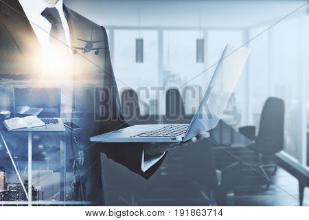 Businessman using laptop on abstract office workplace and flying airplane background. Double exposure