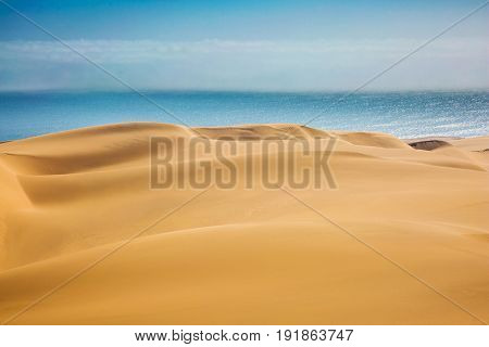 The concept of exotic and extreme travel. Atlantic in Namibia, Africa. Giant sand dunes on the ocean coast
