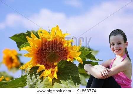 Field of sunflowers. Beautiful girl smiling near a large sunflower