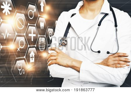 Young female doctor with folded arms standing on dark background with digital medical icons. Reserach concept
