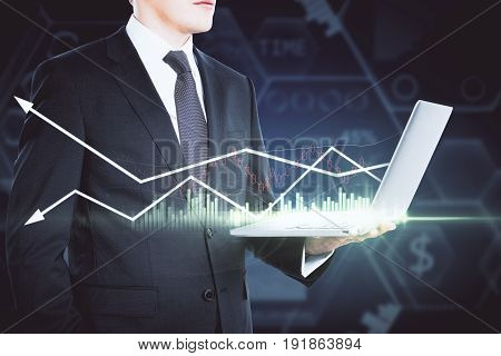 Side view of businessman using laptop with forex chart. Blurry dark background. Stock exchange concept
