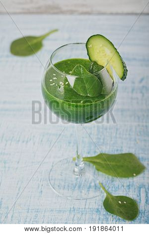 Wine glass filled with fresh green spinach and cucumber smoothie on light blue wooden background. Non-alcoholic drinks. Healthy food and vegetarian concept.